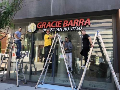 Signarama Toronto Our People putting up Gracie Barra sign
